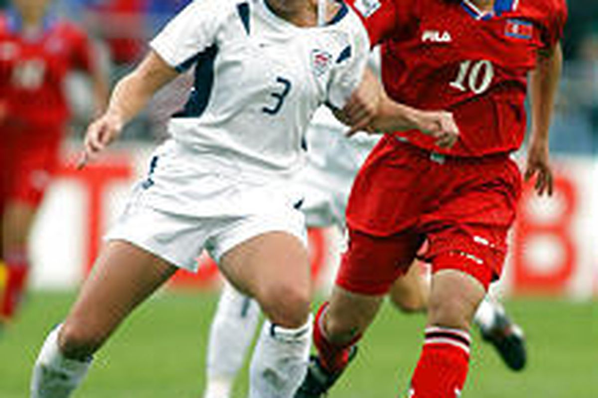 USA's Christie Pearce (3) and North Korea's Jin Pyol Hui (10) battle for the ball.