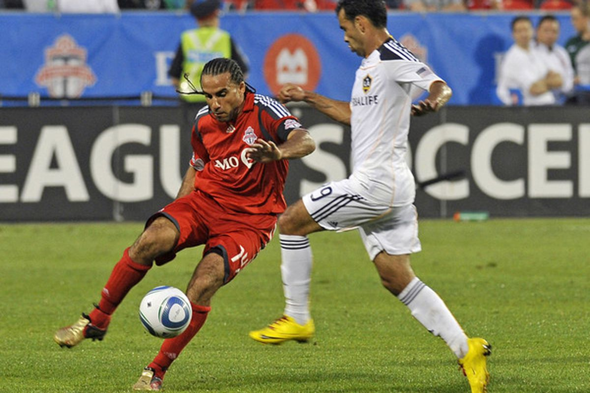 Dwayne De Rosario (14) of the Toronto FC looks to pass the ball as Juninho of the Los Angeles Galaxy defends during game action June 26, 2010 at BMO Field in Toronto, Ontario, Canada. (Photo by Brad White/Getty Images)