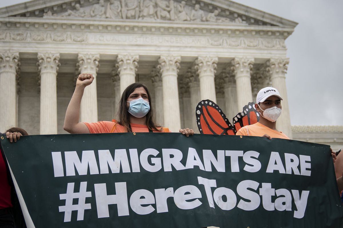 """Protesters in front of the US supreme Court hold a banner that reads """"Immigrants are #HereToStay."""""""