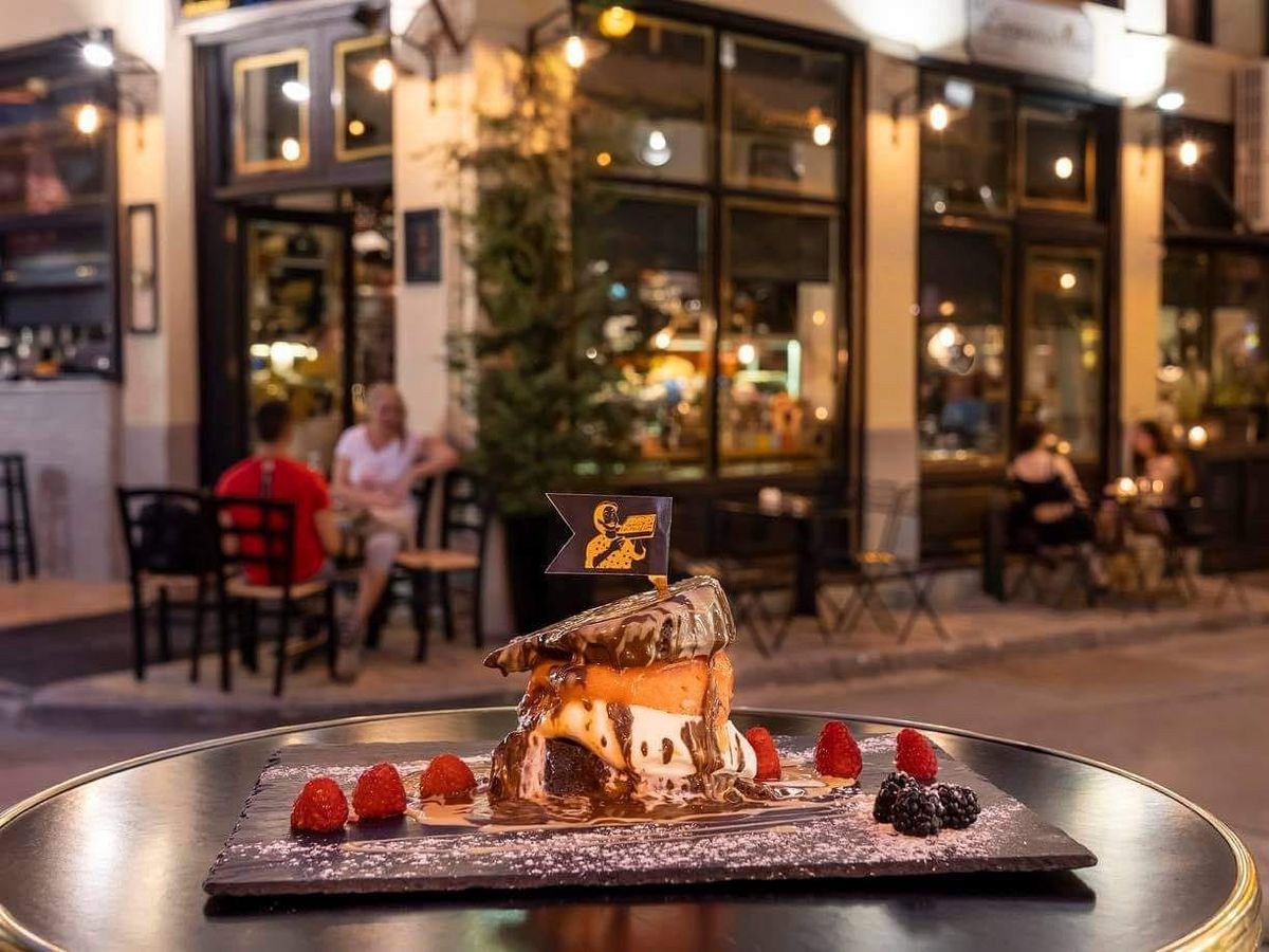 An outdoor table in front of a cafe exterior at night. On the table is a dessert, a stack of cake, doughnut, ice cream, and chocolate sauce, surrounded by raspberries