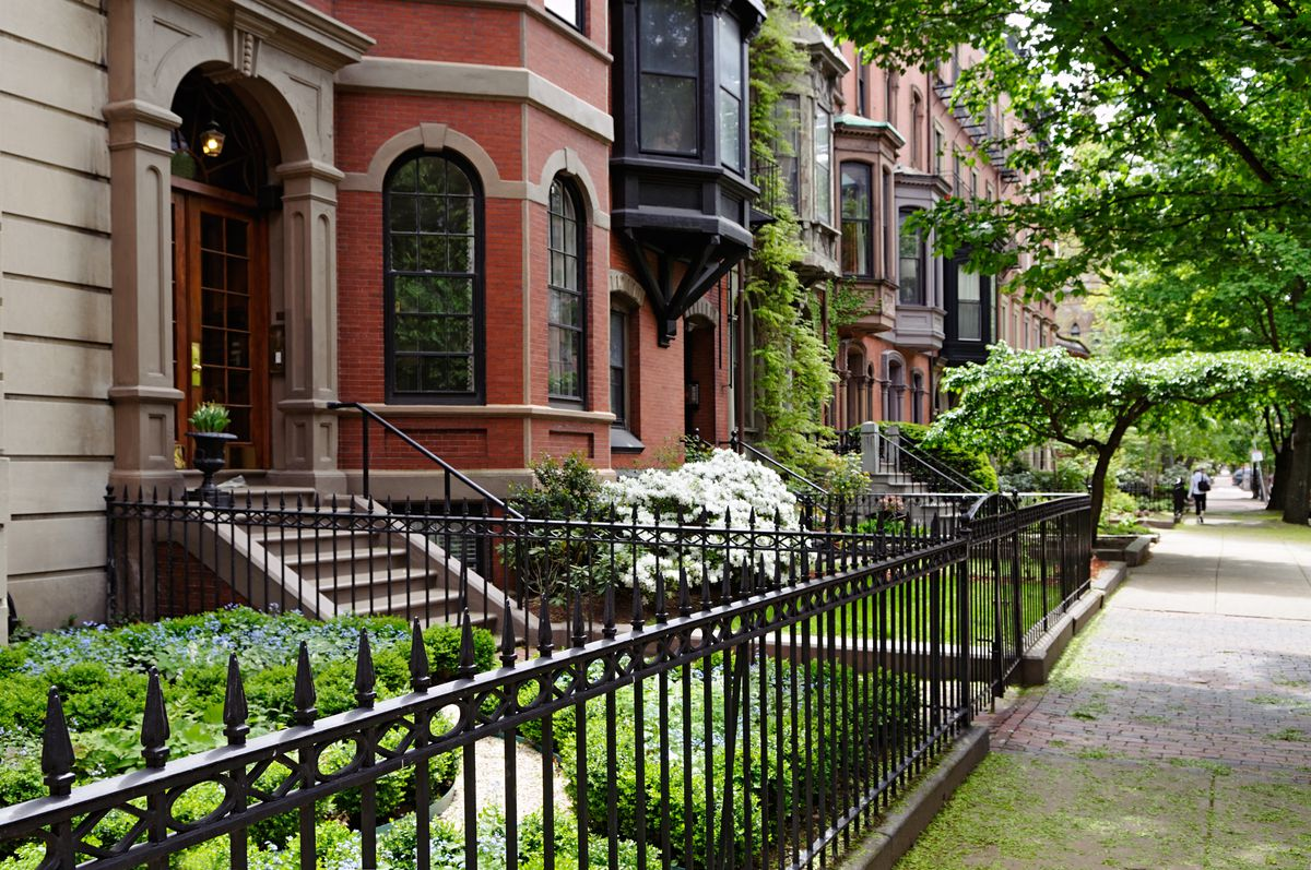 Townhouses along a lush street, with iron fences in front of their small front yards.
