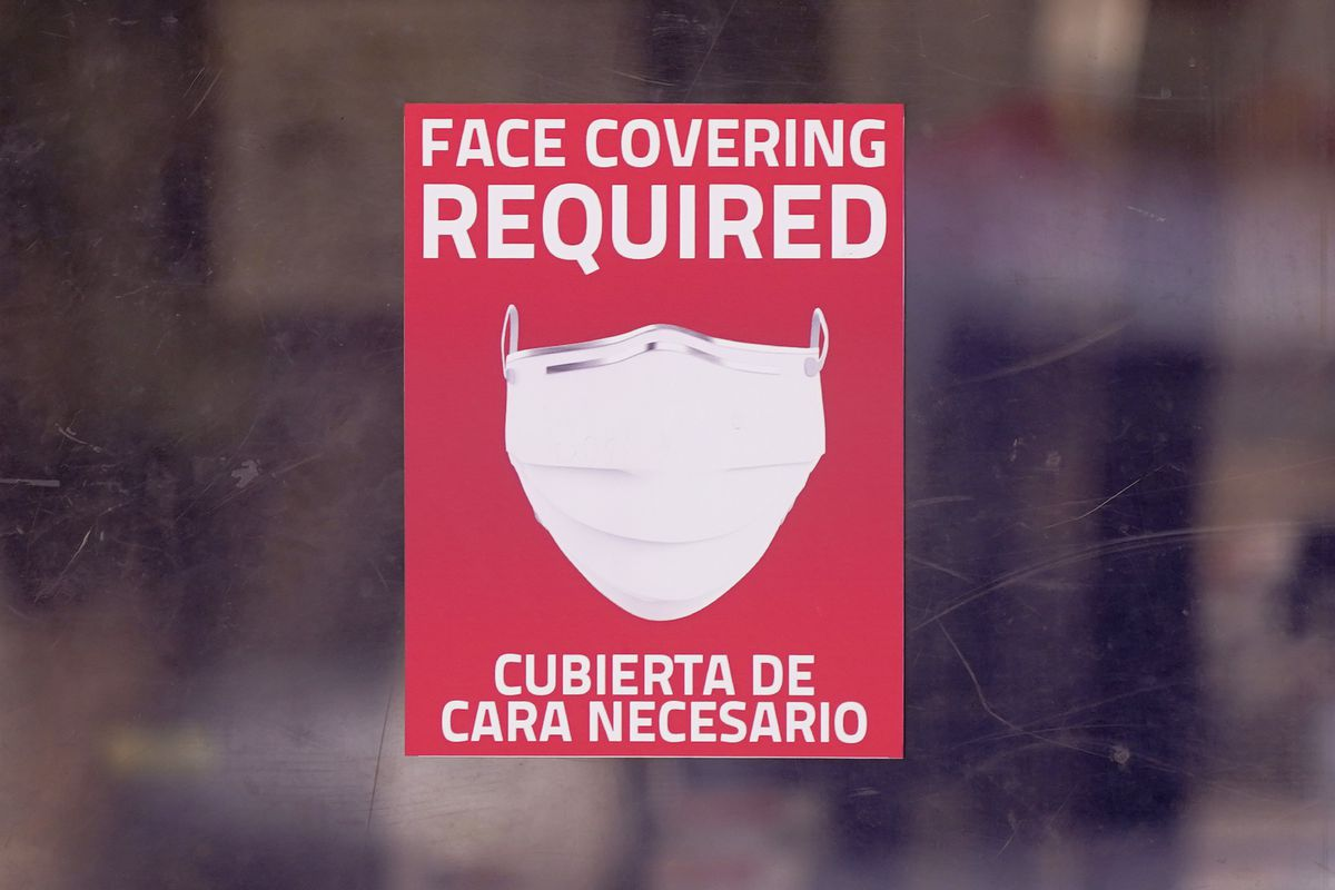 A mask required sign is displayed on the entrance to a business Tuesday, March 2, 2021, in Dallas.
