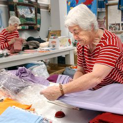 From left, Dorothy Arnold and May Arnold work on quilts at the Humanitarian Service Room at Deseret Industries in Murray on Dec. 4, 2001.