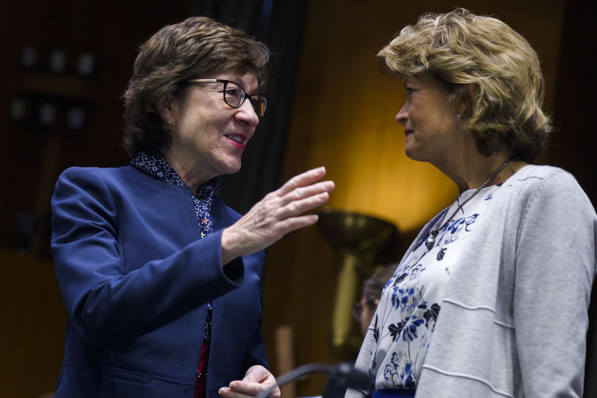 Collins, in a blue suit and black glasses, smiles as she gestures. Murkowski, in a grey sweater and a dress with a blue and white floral print, appears to nod. Behind them are the ornate bowl-shaped sconces of the Senate building.