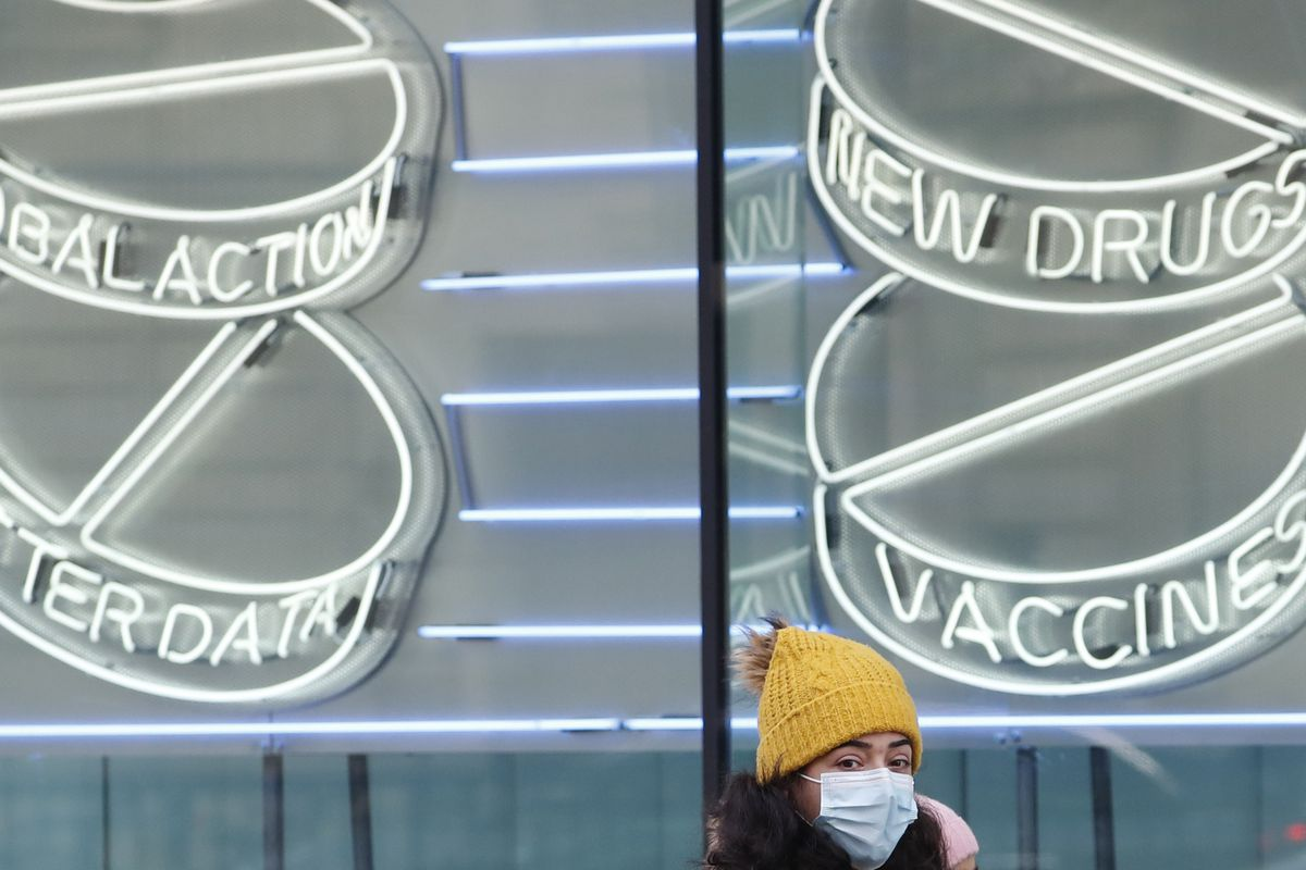 A woman wearing a mask against coronavirus walks past a neon sign display at the Wellcome Institute in London, Tuesday, Feb. 2, 2021. A new study suggests cases of the new UK COVID-19 variant are doubling every 10 days.