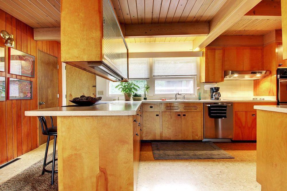 A midcentury modern kitchen with wood walls, cabinetry, and ceiling. The floor is linoleum. There are works of art hanging on one wall.