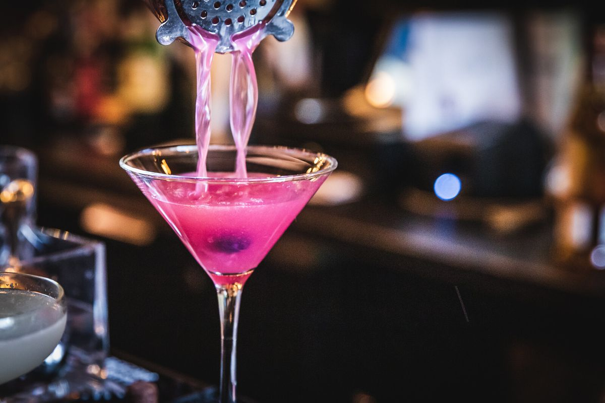 A bright pink cocktail flows out of a shaker and into a martini glass.