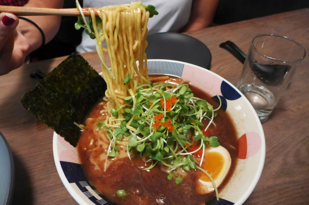 A bowl of ramen with noodles being pulled out of the broth, some sprouts floating on the broth, and a halved, boiled egg