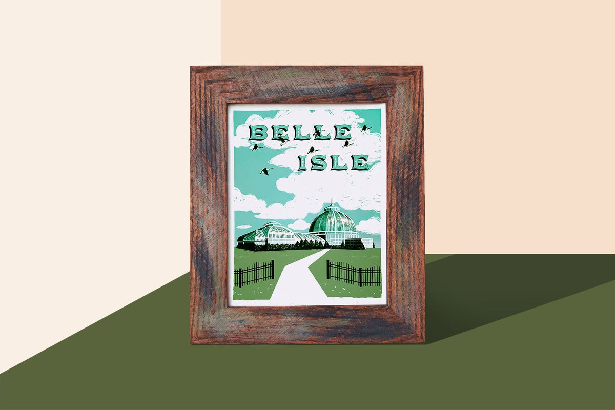 A wooden picture frame with a print that depicts a road with grass on both sides and words that read: Belle Isle sits in front of a colorful geometric patterned background.