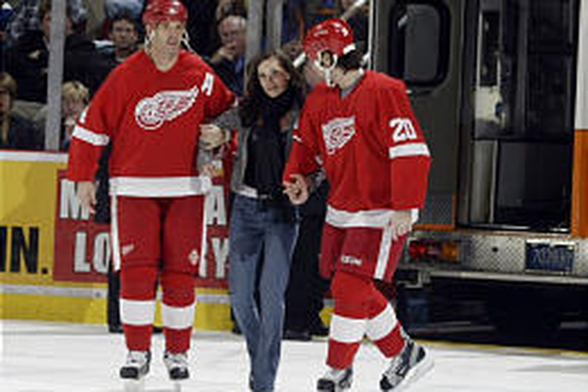Detroit's Brendan Shanahan, left, and Robert Lang help Jiri Fischer's fiancee to the Wings bench as medical personnel work on Fischer after he had a seizure during the first period.