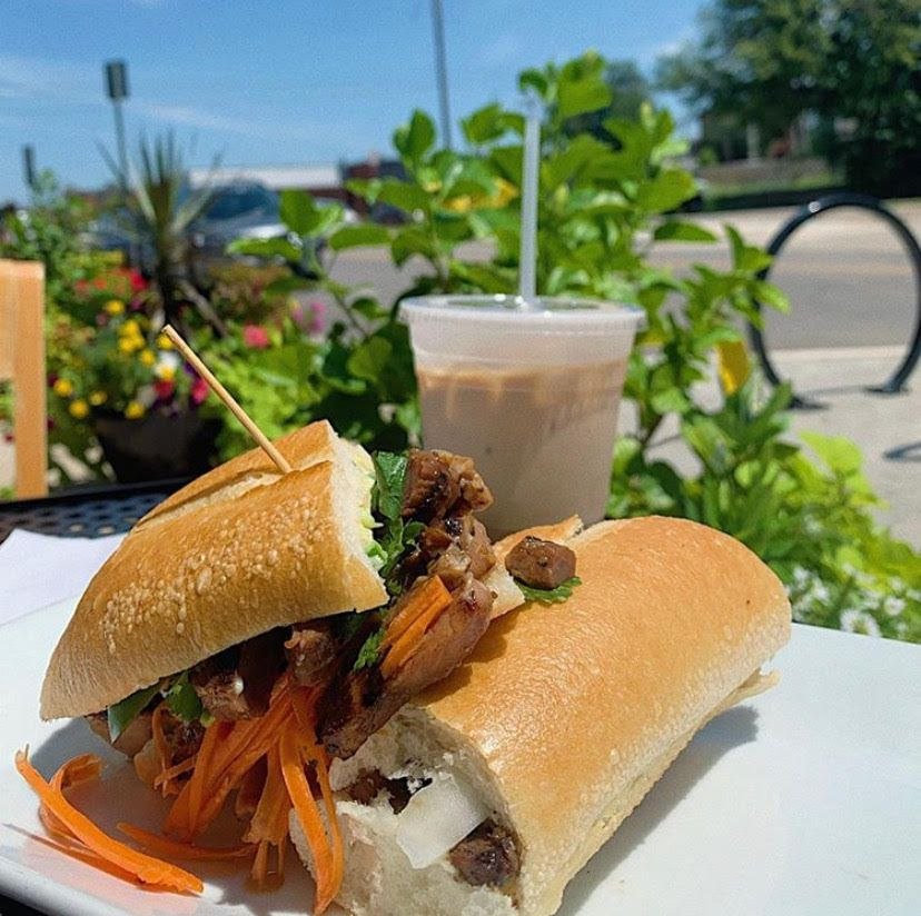A banh mi sandwich on an outdoor table with a to-go drink