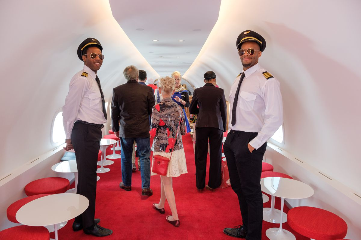 Two men in pilots' uniforms and aviator sunglasses  are in a small airplane bar with red carpeting.