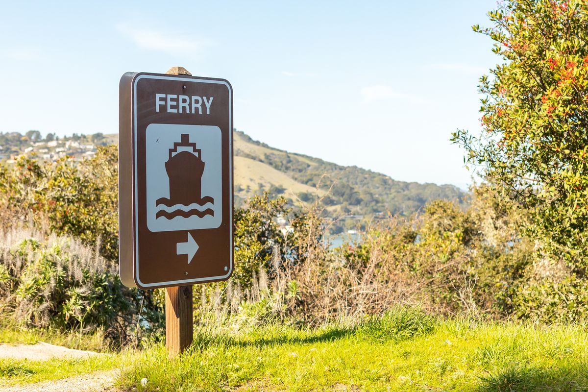 """A sign reads """"ferry"""" with an arrow pointing to the right."""