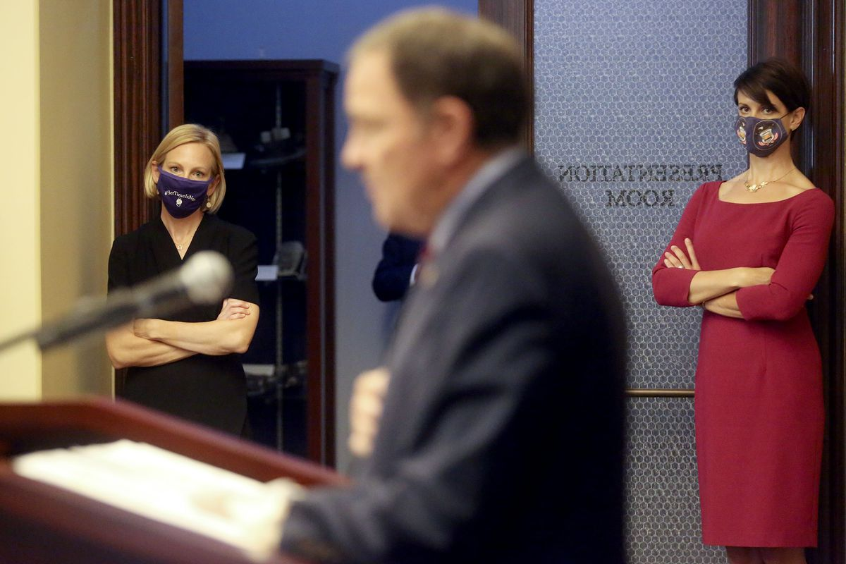 Dr. Emily Spivak, associate professor of infectious disease at University of Utah Health, left, and state epidemiologist Dr. Angela Dunn, right, listen as Gov. Gary Herbert speaks during a COVID-19 press conference at the Capitol in Salt Lake City on Thursday, Oct. 8, 2020.