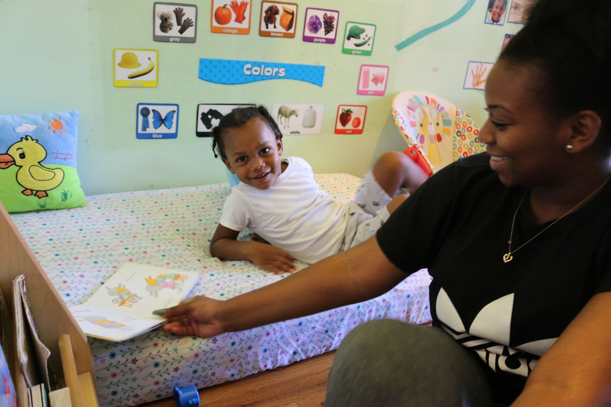 Kiara Dash, an assistant at Little Minds at Work, reads to Thravis Ealey. (Photo: Christina Veiga)
