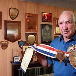 Gene Fullmer holds up World Middleweight Championship belt, he won from his fight with Sugar Ray Robinson in 1957.