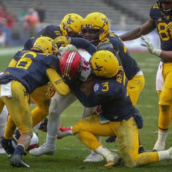 Utah Utes linebacker Jake Jackson (44) is wrapped up by the West Virginia Mountaineers defensive line during the Zaxby's Heart of Dallas Bowl between the Utah Utes and the West Virginia Mountaineers in Dallas Texas on Tuesday, Dec. 26, 2017.