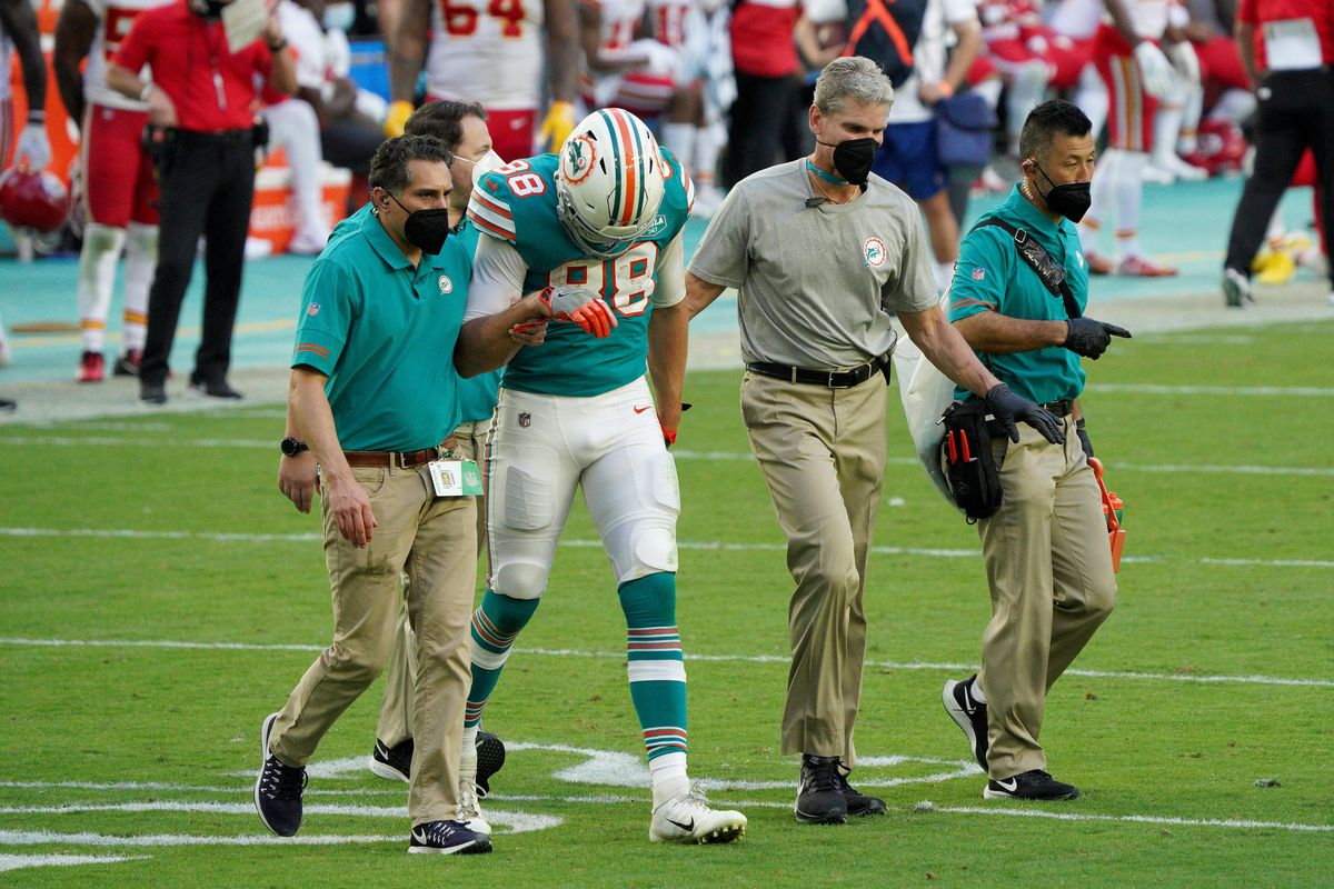 Mike Gesicki #88 of the Miami Dolphins is escorted off the field against the Kansas City Chiefs during the second half in the game at Hard Rock Stadium on December 13, 2020 in Miami Gardens, Florida.