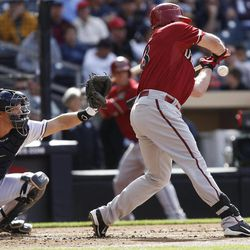 Arizona Diamondbacks' Jason Kubel, right, checks his swing as San Diego Padres catcher Nick Hundley prepares to a catch ball four that forces in a run from third base during the first inning of a baseball game on Wednesday, April 11, 2012 in San Diego. It was the third run the Padres' pitchers have forced in during their five-plus games this season.