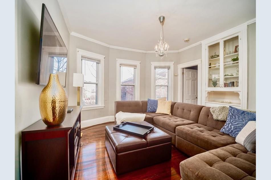A living room with a sectional couch and built-in cabinets and drawers and a bay window.