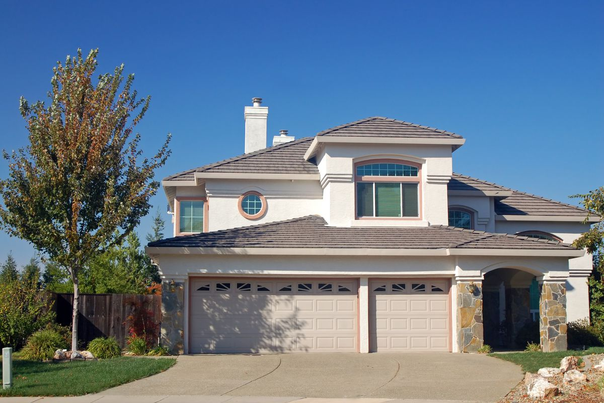A California home with stone detailing, double garage, and circular window above garage.