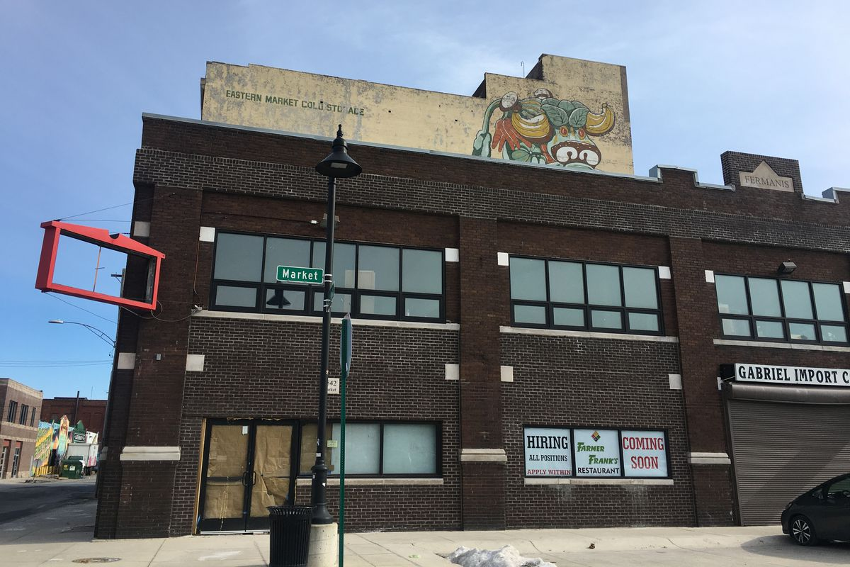 """A wide shot of the brick building where Farmer's Restaurant's sign used to hang. The windows are papered over and there's a sign in several reading """"Farmer Frank's Restaurant Coming Soon."""""""