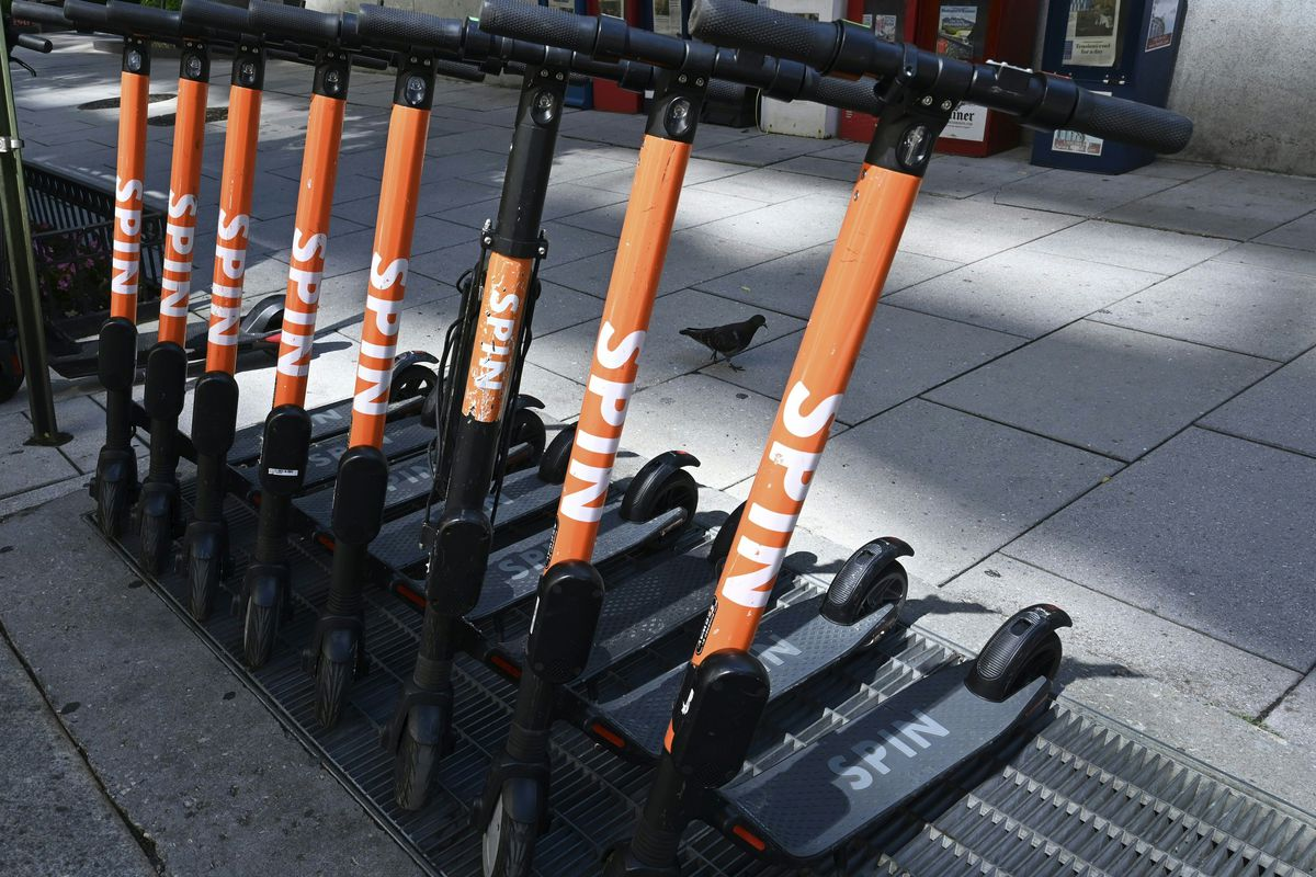 """A row of identical black scooters with the word """"spin"""" in orange and white on the handles."""