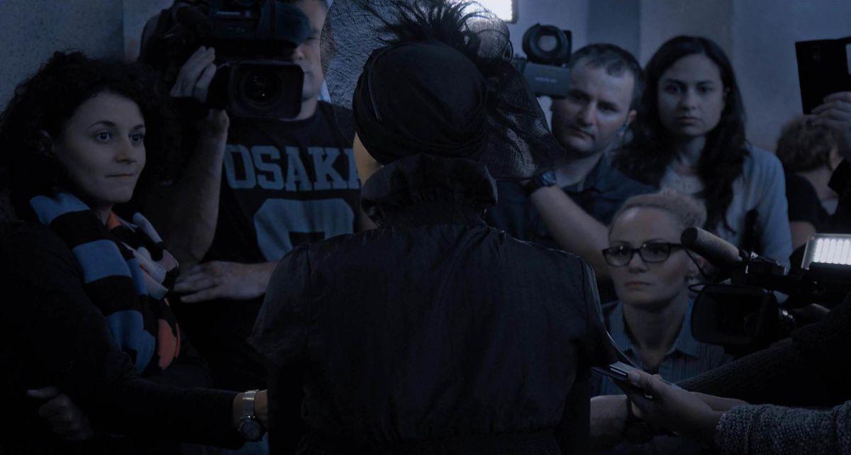 Journalists face a man.