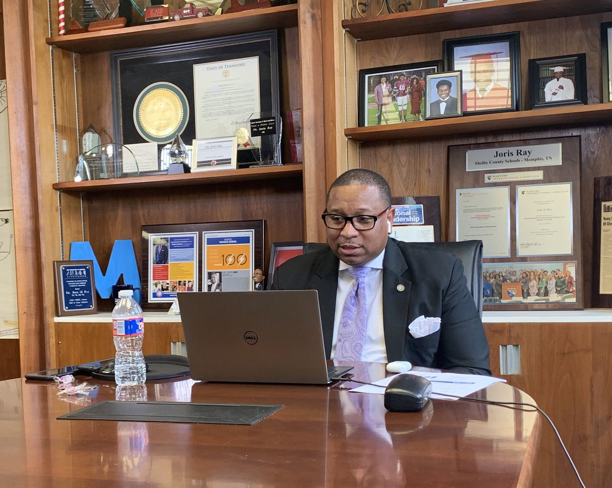 Superintendent Joris Ray sits at a conference table alone in front of a laptop.