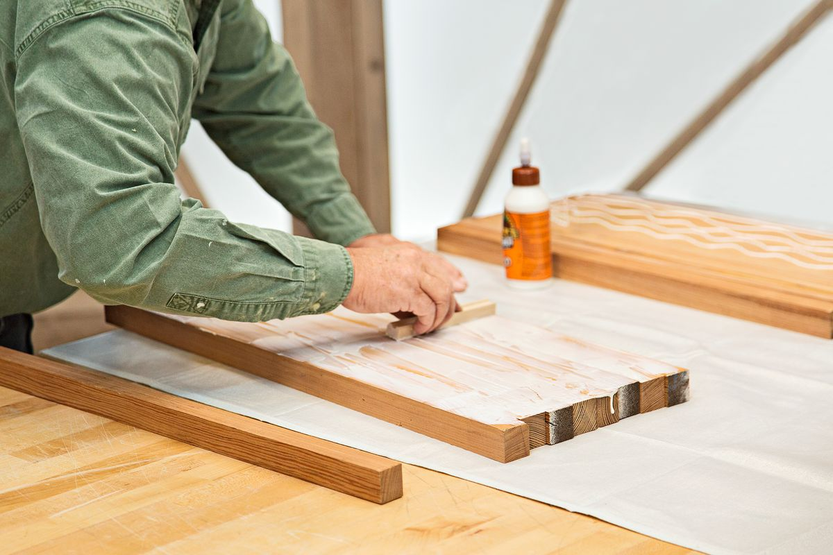Person applying wood glue to strips of wood that will soon form an edge grain cutting board.