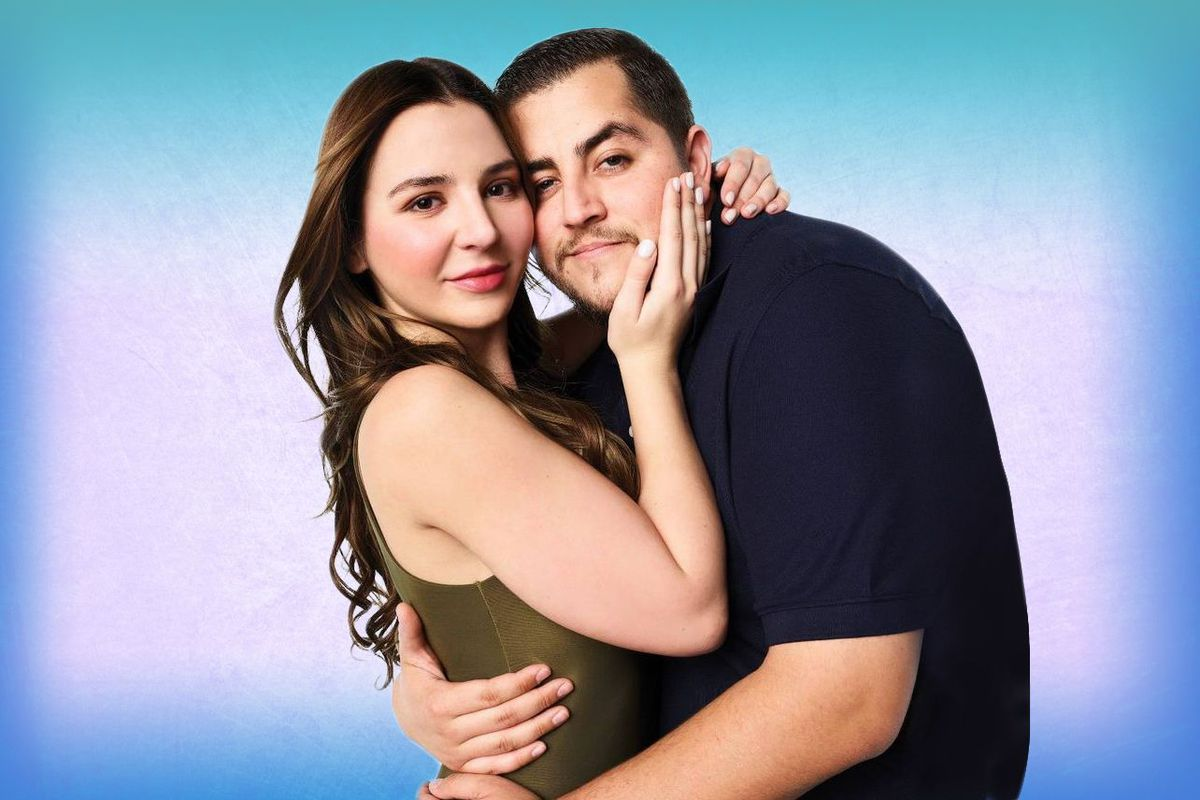 A couple embraces and looks at the camera, against a colorful backdrop.