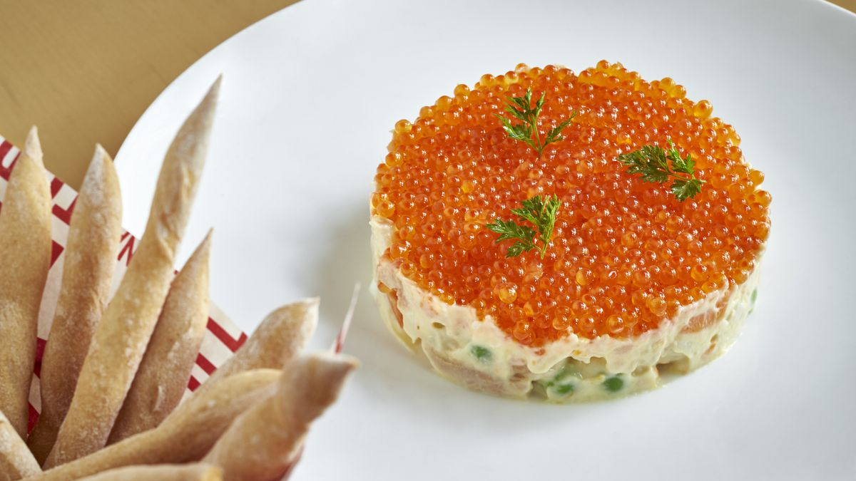 A fancy disc of Spanish trout roe on white plate with a side of breadsticks.