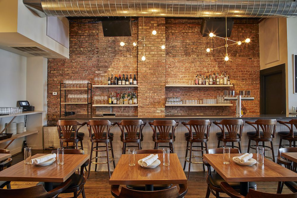 A restaurant bar with wooden bar stools and a rear brick wall.