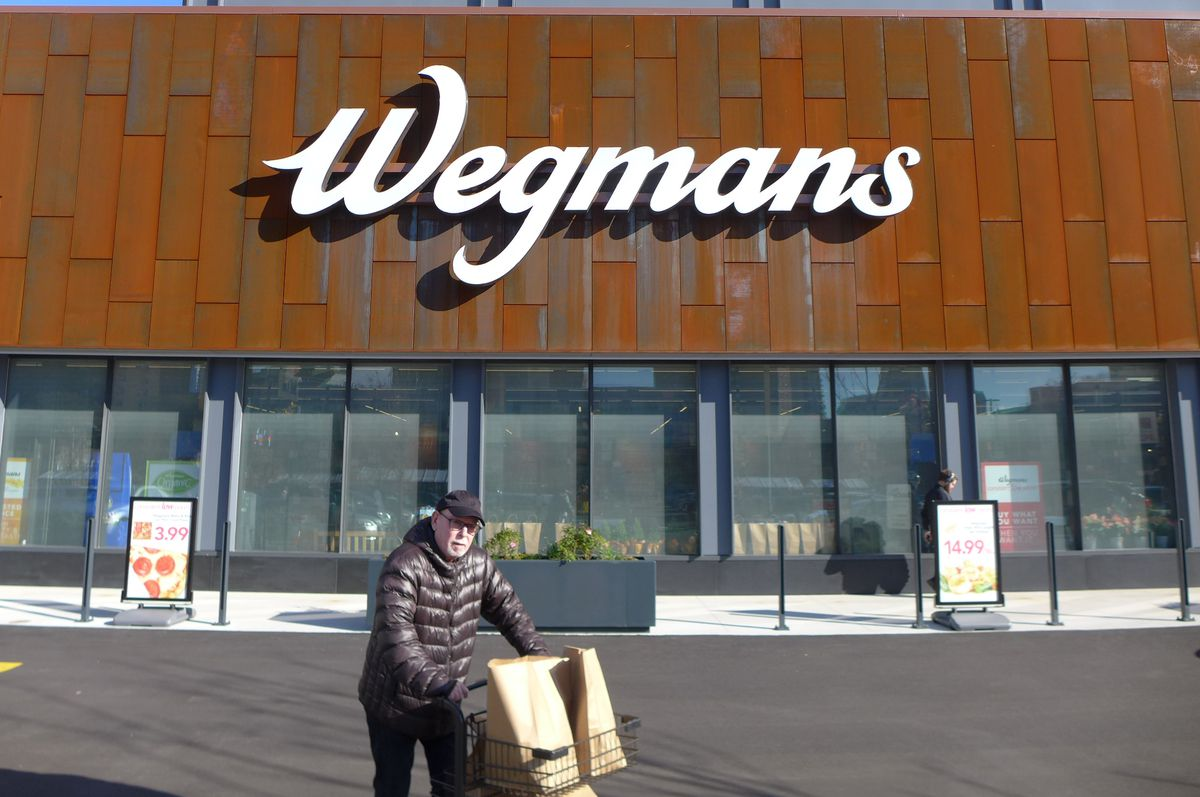 A man pushing a cart full of groceries in the bright sunlight in front of Wegmans.