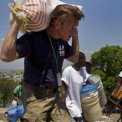 American actor Sean Penn carries the belongings of a person displaced by the earthquake as people are relocated from the Petion ville Golf Club to a new camp, Corail-Cesselesse, in Port-au-Prince, Saturday, April 10, 2010. Haiti's government is beginning to relocate thousands of people in a multi-agency effort to move people to higher ground before the rainy season.