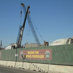 """The """"humps"""" of three concrete trucks lined up on Clark Street behind the construction fence -"""