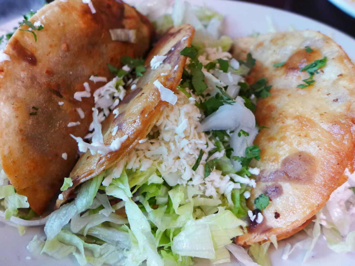 A couple of tacos with deep fried shells that make them look puffy, filled with potato cubes.