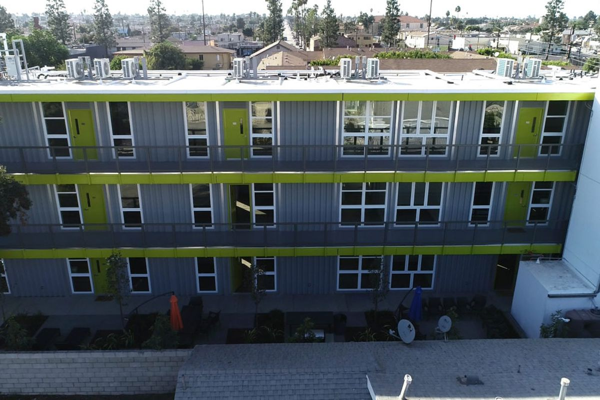A bright green and gray apartment building made from shipping containers is shown in an LA neighborhood with smaller houses in the background.