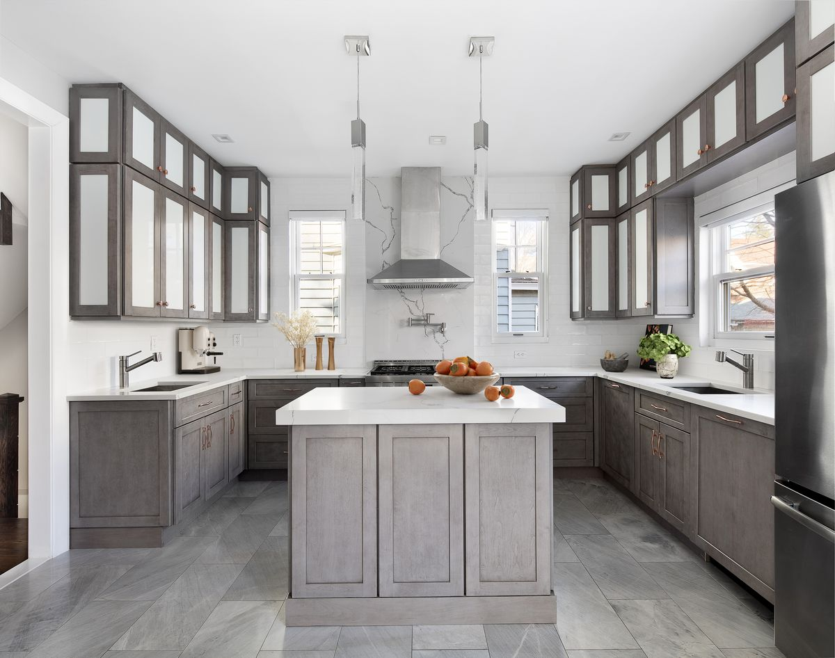 A kitchen with a large island made from gray wood, gray floor tiles, and gray cabinets.
