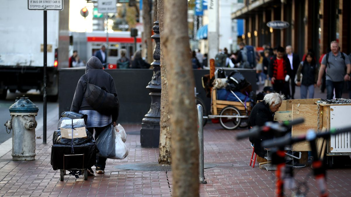 A homeless man pulls a cart heavy with belongings down a brick sidewalk filled with people.