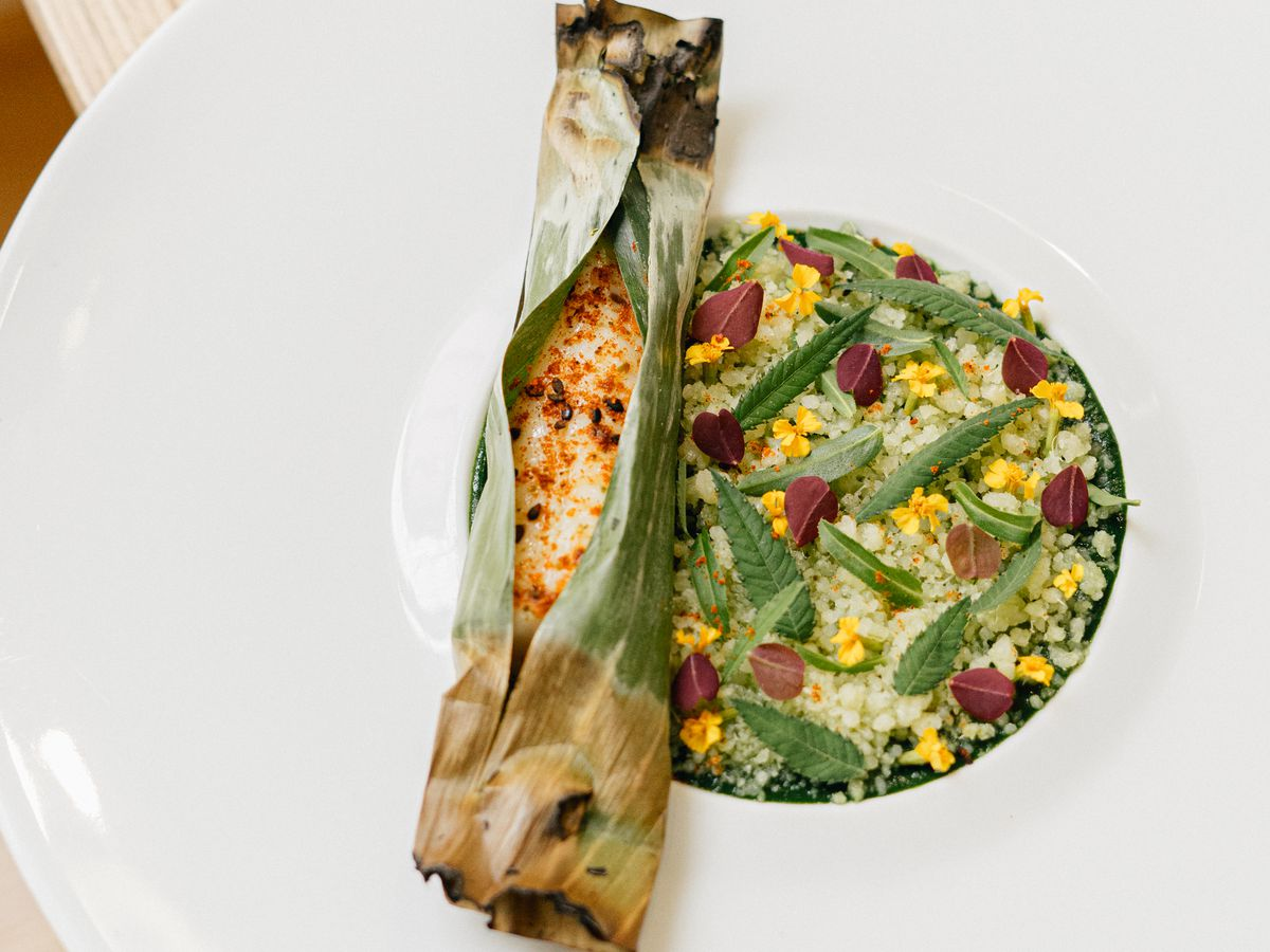 Roasted fish wrapped in a cylinder of banana leaf, resting to one side of a couscous salad dotted with herbs and flowers