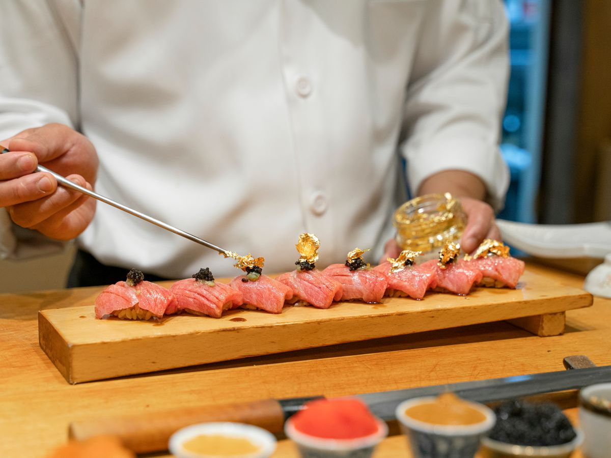 A sushi chef in chef whites carefully places gold foil on top of thin slices of pink sushi