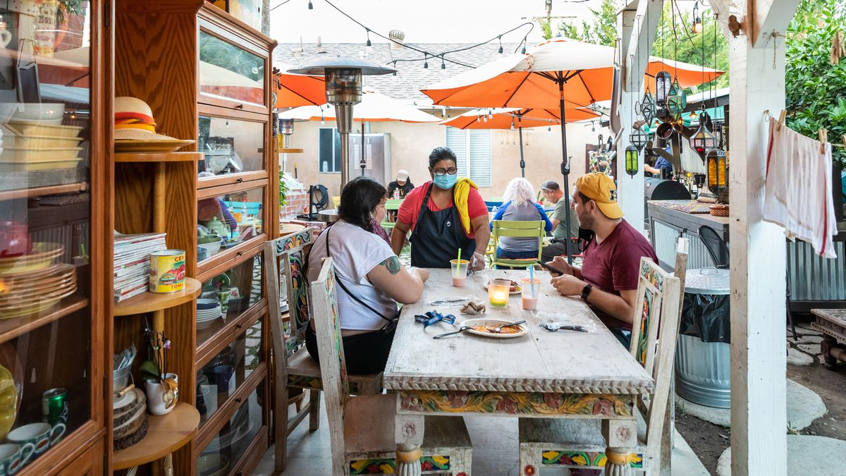 The outdoor dining area of Barra de Pan in Corona, California, operated by Lucy Silva in her backyard with wood shelving and tables with patrons.