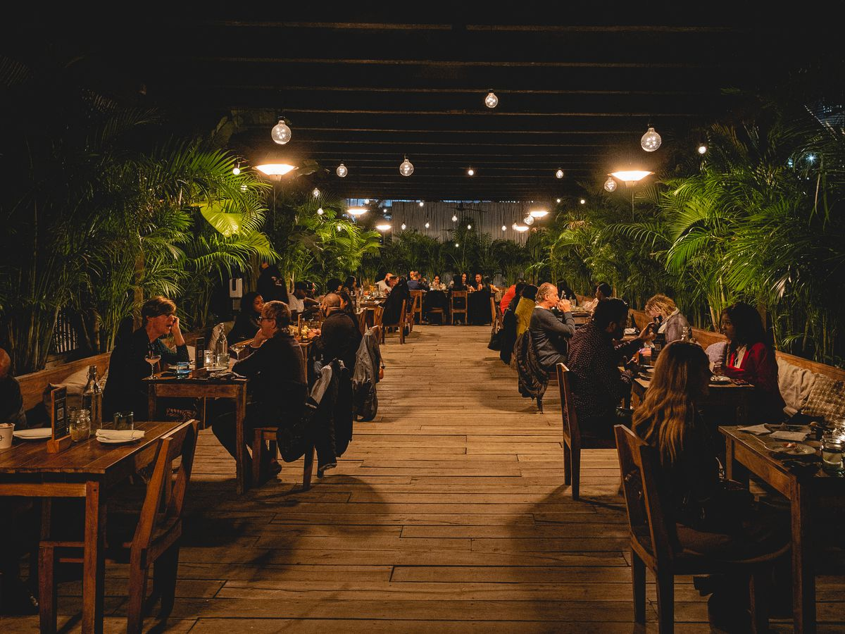 The outdoor space of a restaurant with wooden chairs and tables, and lush green plants