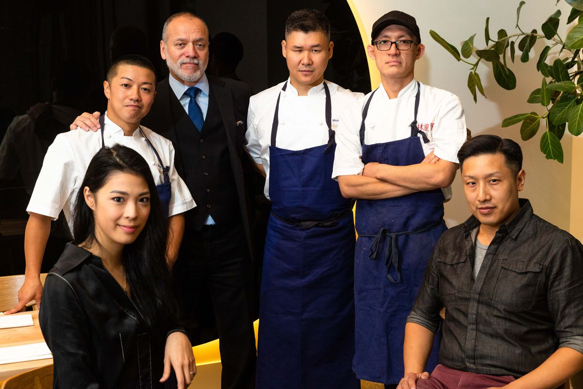 A group of people including three men in chef aprons, a man in a suit, and a woman and man in black sitting down
