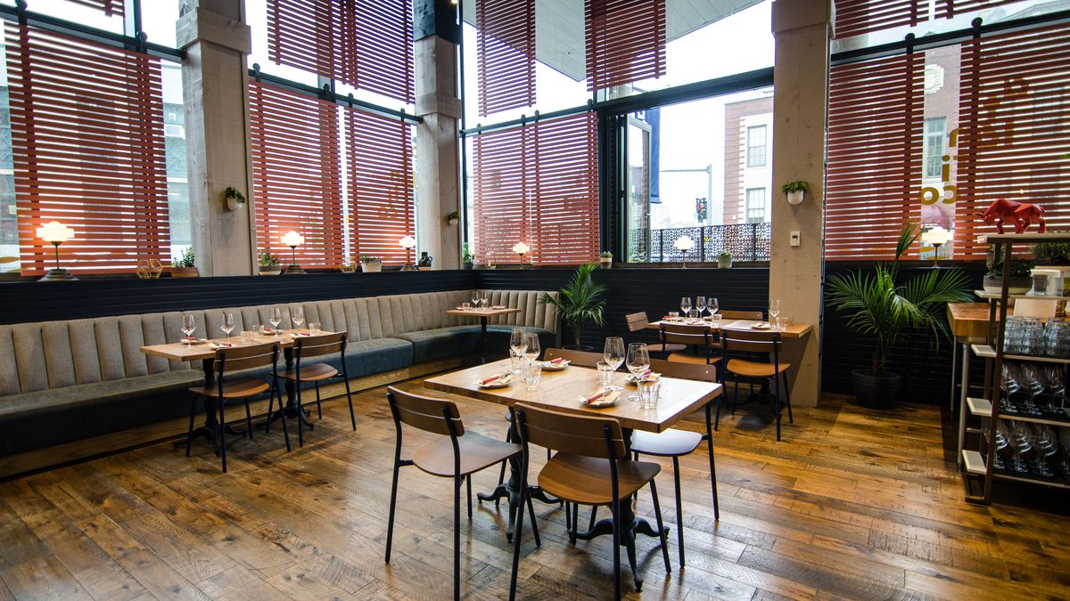 A high-ceilinged restaurant interior features a wooden floor, wooden tables and chairs, off-white banquettes and accents, navy blue accents, and rose slats over the windows.