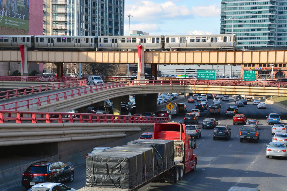 A multilane highway in an urban setting full of cars and trucks running under overpasses and an elevated train.