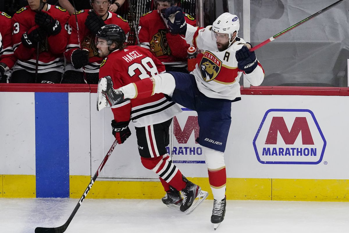 Panthers defenseman Aaron Ekblad, right, is checked by Blackhawks left wing Brandon Hagel during Thursday's game.