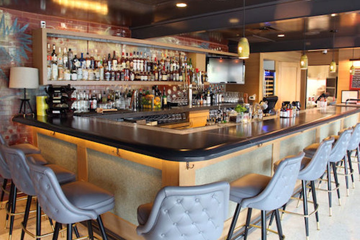 A bar with lots of liquor bottles and quilted barstools