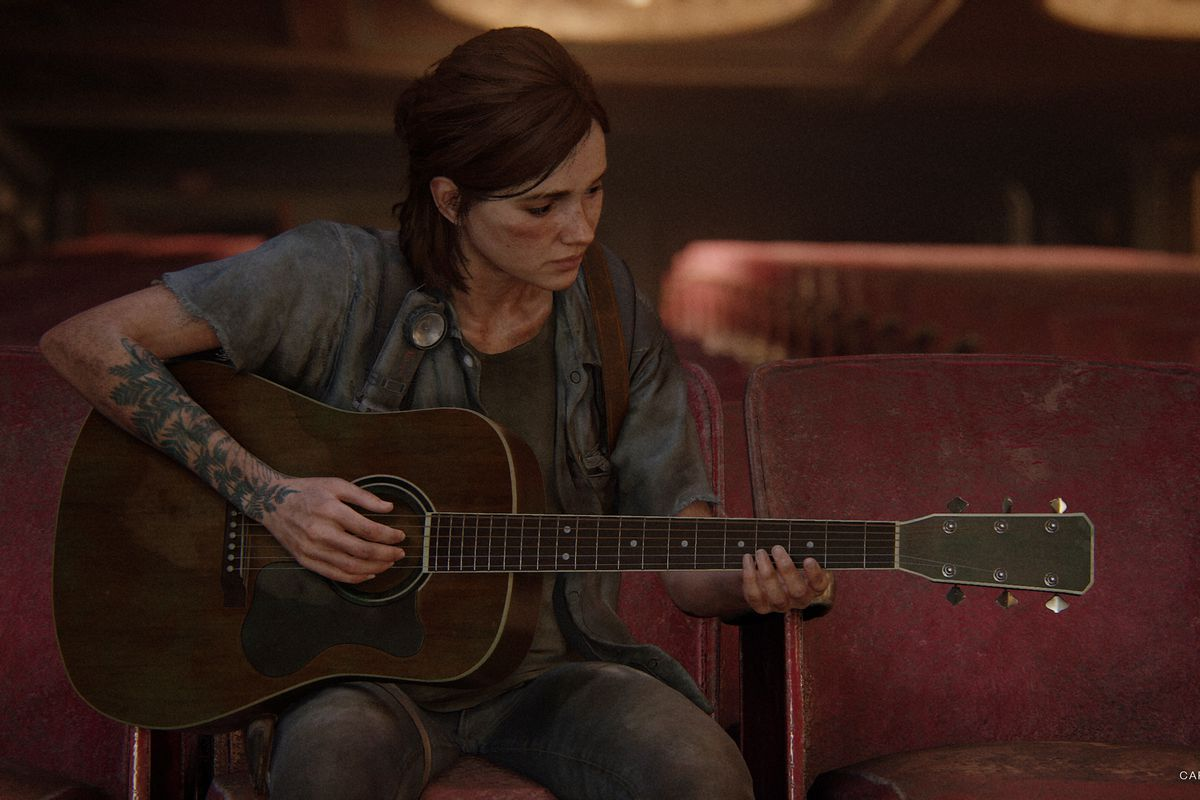Ellie seated in the audience of a theater, playing the guitar in The Last of Us Part 2